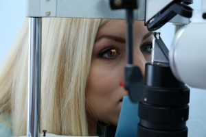 Optometry concept - pretty young woman having her eyes examined